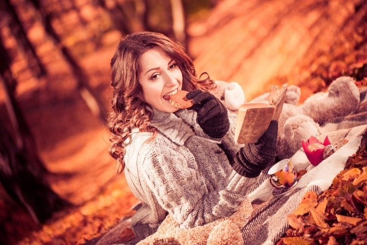 brunet-with-cookie-at-fall-forest-picture-id520980597