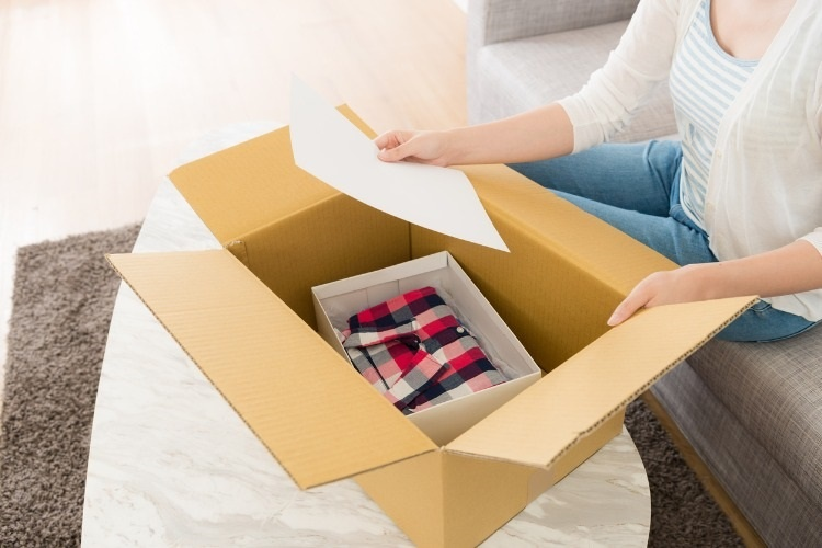 woman-opening-personal-online-shopping-parcel-picture-id1015255538