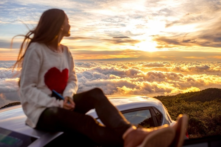 woman-enjoying-beautiful-cloudscape-picture-id513108430