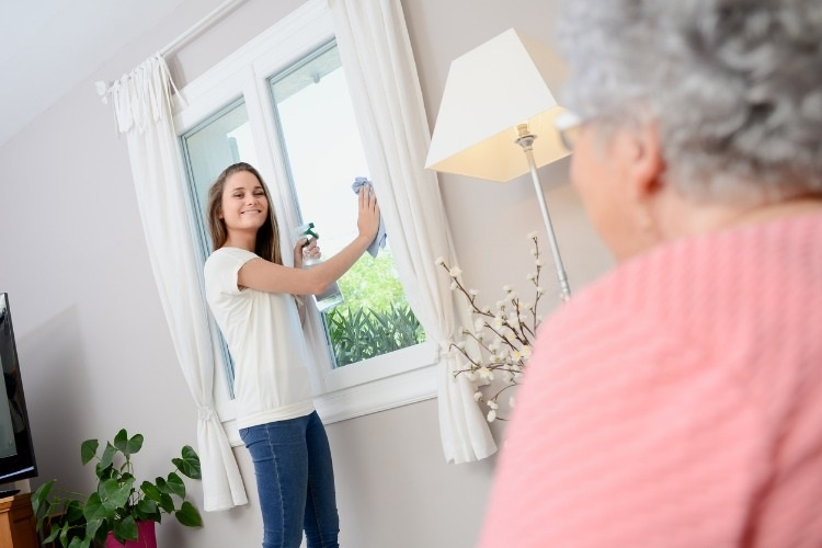 cheerful-young-girl-helping-with-household-chores-elderly-woman-home-picture-id626585164_01
