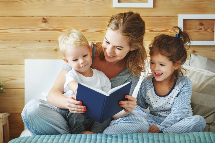 family-mother-reading-to-children-book-in-bed-picture-id886402190