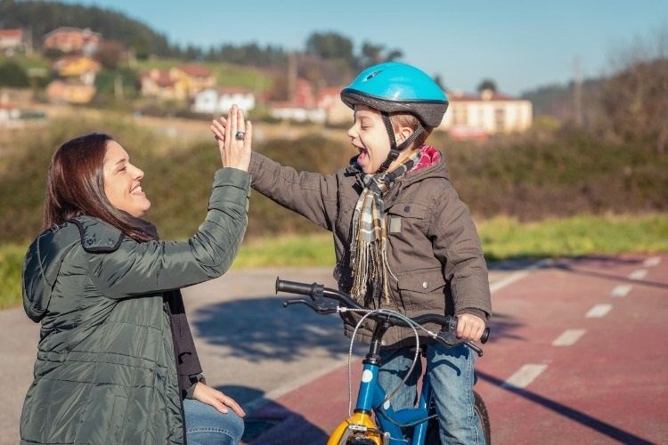 mother-and-son-giving-five-by-success-riding-bicycle-picture-id973108978