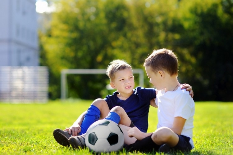 two-little-boys-playing-a-soccer-game-on-sunny-summer-day-picture-id671499674