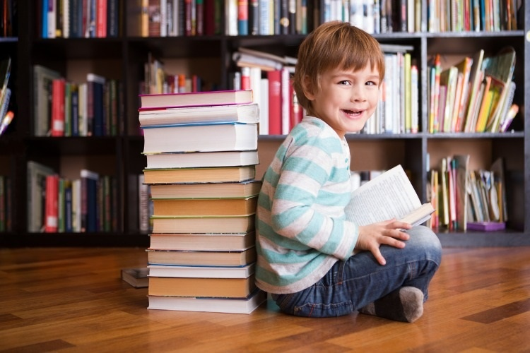 preschooler-little-boy-reading-a-book-in-the-library-the-little-boy-picture-id906233806