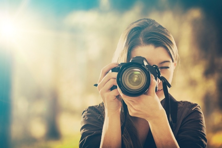 portrait-of-a-photographer-covering-her-face-with-camera-picture-id664304668