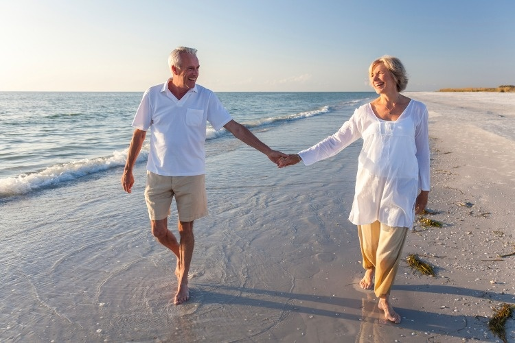 smiling-senior-couple-holding-hands-on-a-beach-picture-id163731040