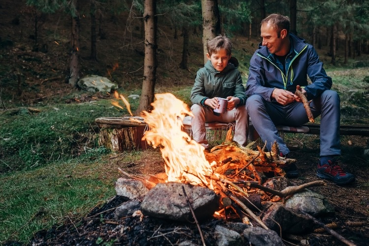 father-with-son-warm-near-campfire-drink-tea-and-have-conversation-picture-id674906646