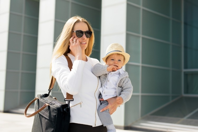 mother-going-to-work-and-talking-on-the-phone-with-baby-in-her-hands-picture-id852047084