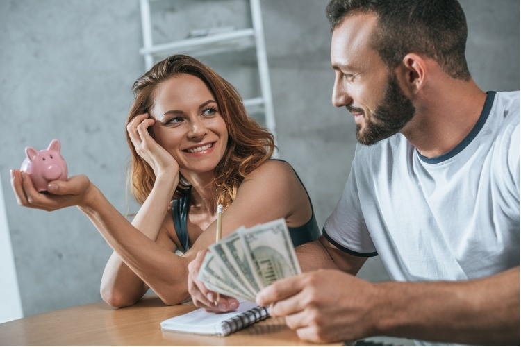happy-couple-planning-family-budget-and-looking-at-each-other-in-picture-id1002878068_1_01
