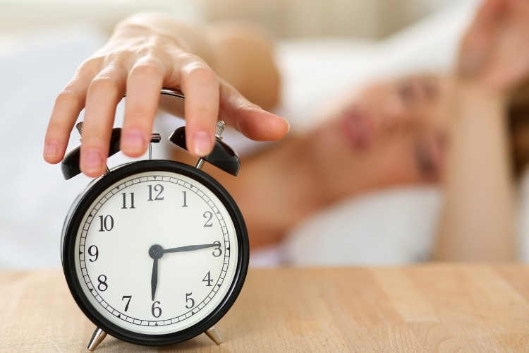stretching-hand-of-sleepy-young-woman-trying-kill-alarm-clock-picture-id520798952