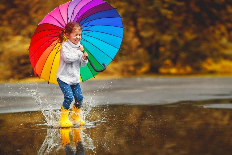 happy-funny-child-girl-with-umbrella-jumping-on-puddles-in-rubber-picture-id836684354