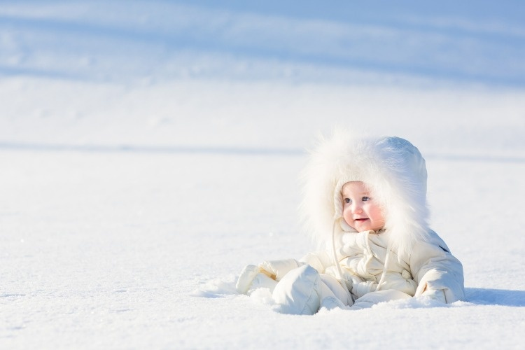 beautiful-baby-in-white-suit-sitting-at-snow-field-picture-id474297959