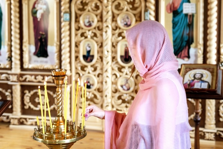young-woman-in-pink-headscarf-praying-near-candles-at-wooden-church-picture-id1013847868_01