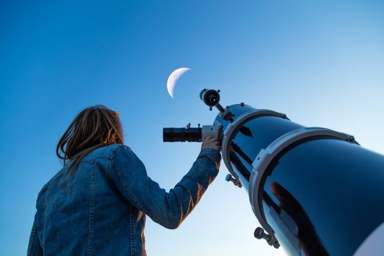 girl-looking-at-the-moon-through-a-telescope-picture-id688387522