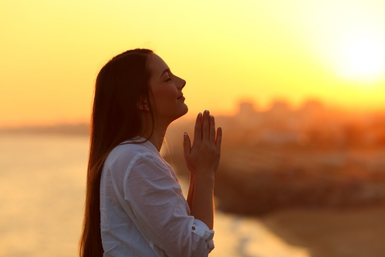 profile-of-a-woman-praying-at-sunset-picture-id915213254
