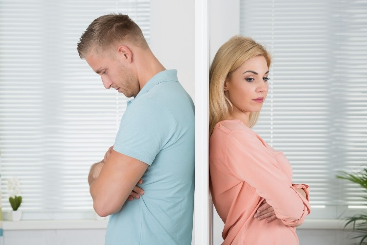 unhappy-couple-standing-back-to-back-at-home-picture-id583989228
