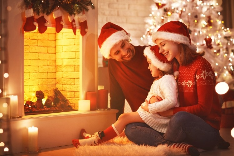 happy-family-sitting-by-fireplace-on-christmas-eve-picture-id873882254_01