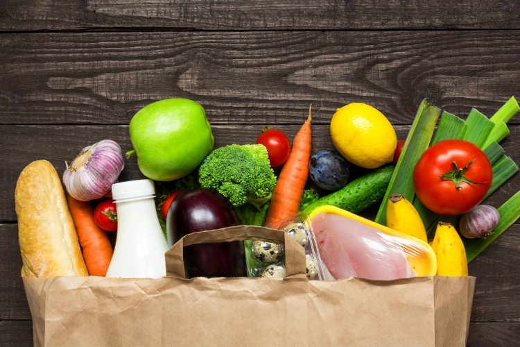 full-paper-bag-of-different-health-food-on-rustic-wooden-background-picture-id836782690