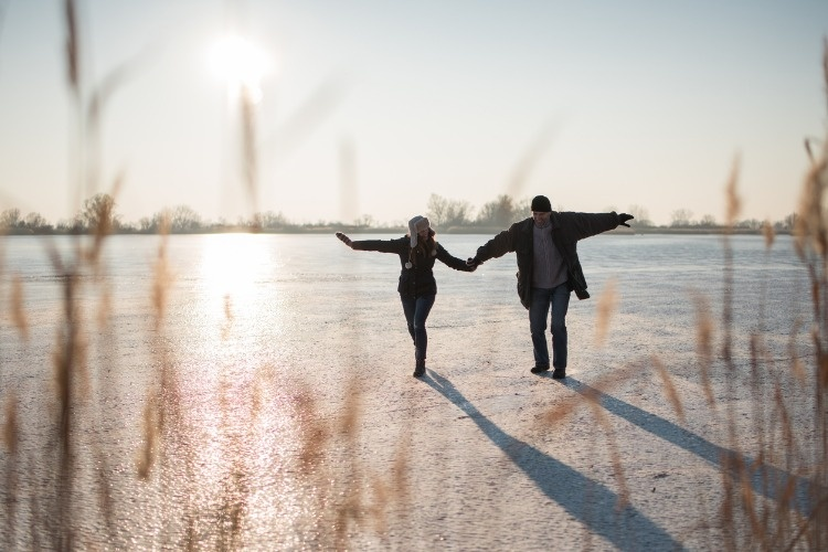couple-stepping-carefully-on-frozen-lake-picture-id879768054
