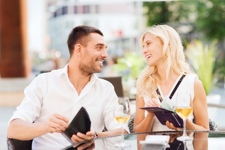 happy-couple-with-wallet-paying-bill-at-restaurant-picture-id498606016_01