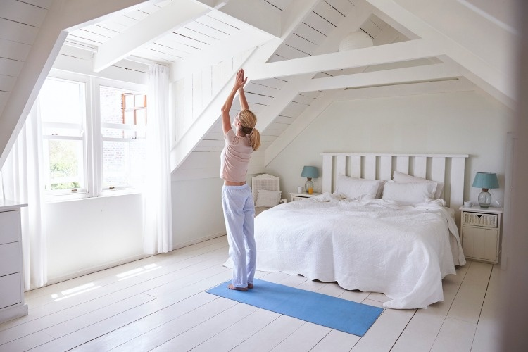 woman-at-home-starting-morning-with-yoga-exercises-in-bedroom-picture-id846715004