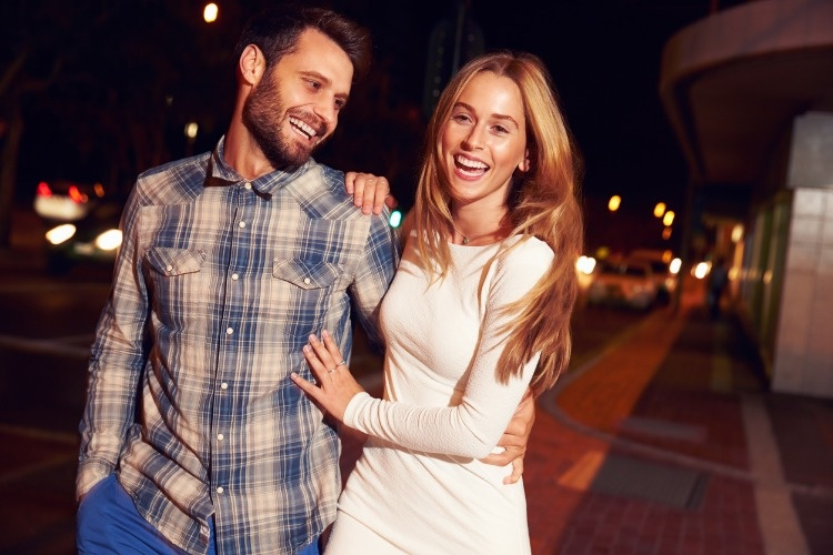 couple-walking-through-town-together-at-night-picture-id478406786