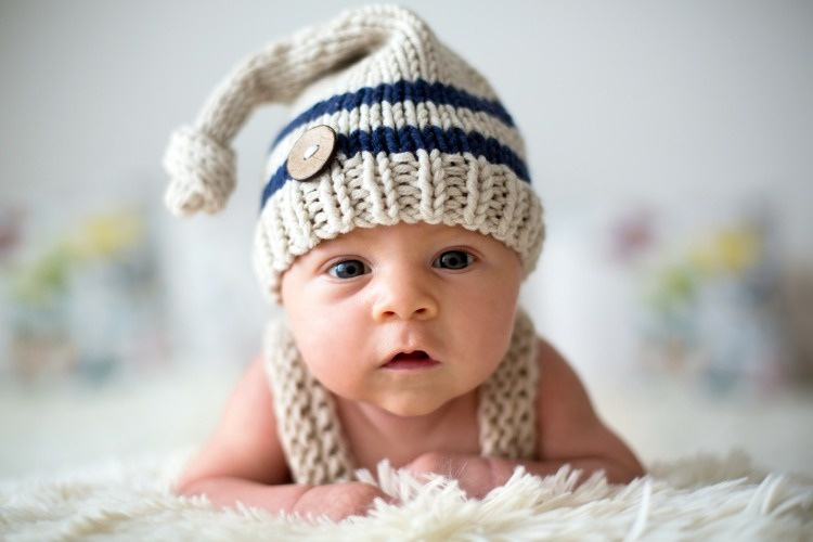 little-newborn-baby-boy-looking-curiously-at-camera-picture-id854489034