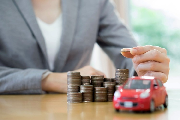 businesswoman-a-toy-car-and-a-stack-of-coins-picture-id544131892