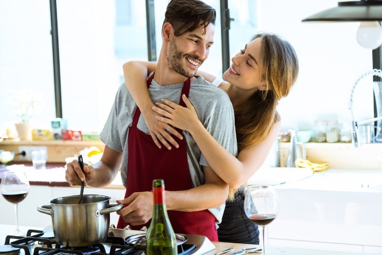 happy-young-couple-cooking-together-in-the-kitchen-at-home-picture-id577306596