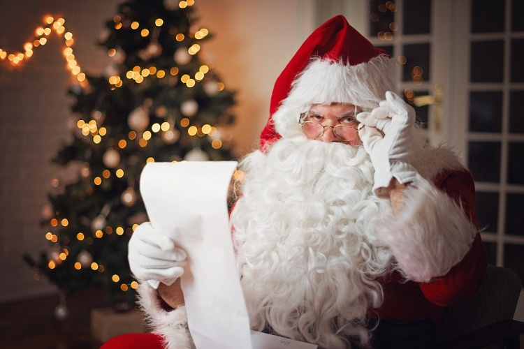 santa-claus-reading-from-a-long-list-in-a-cozy-room-picture-id1047744902