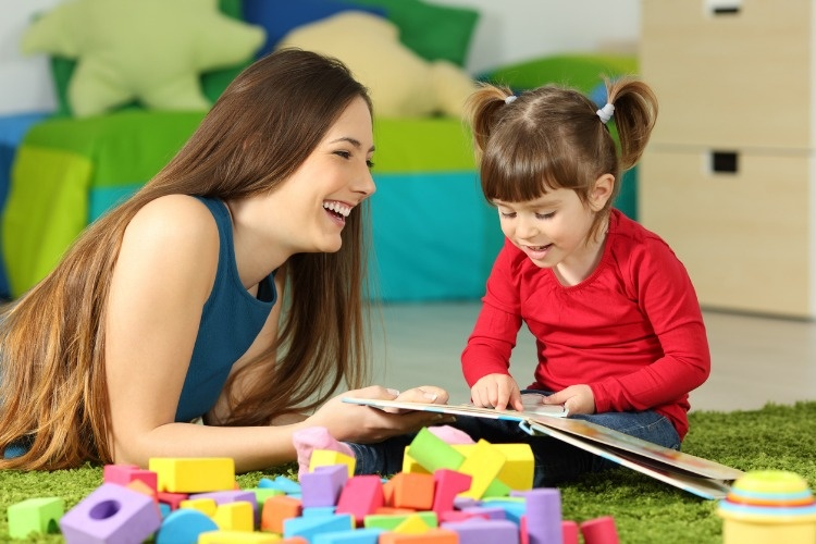 mother-and-toddler-playing-with-a-book-picture-id810756600