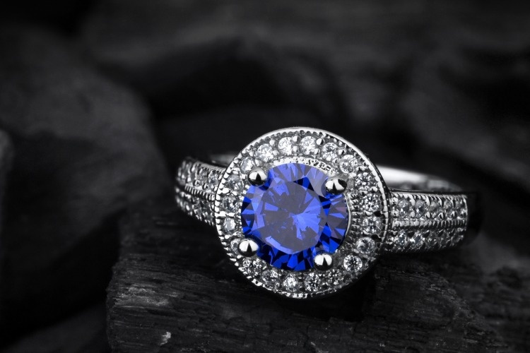 jewelry-ring-witht-big-blue-sapphir-on-black-coal-background-picture-id865506324