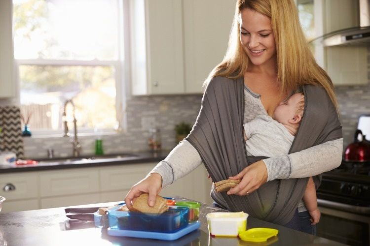 mum-preparing-lunchbox-while-baby-sleeps-on-her-in-picture-id524157522
